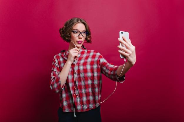 Despreocupada garota de cabelos castanhos na camisa quadriculada casual, fazendo selfie foto interna de alegre jovem de óculos posando com beijo de expressão facial e usando o telefone.