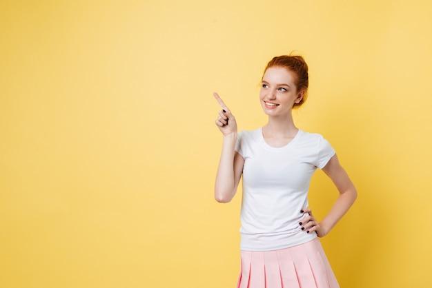 Despreocupada garota ruiva apontando para fora e segurando o braço no quadril