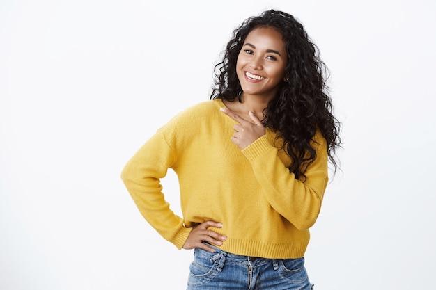 Despreocupada jovem afro-americana moderna com cabelo encaracolado em um suéter amarelo, incline a cabeça com alegria e sorria, observe a câmera enquanto discute uma nova promoção legal, apontando para o espaço em branco esquerdo sobre a parede branca