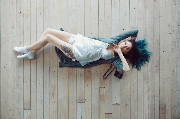 Despreocupada jovem casual bonita deitado no chão de madeira