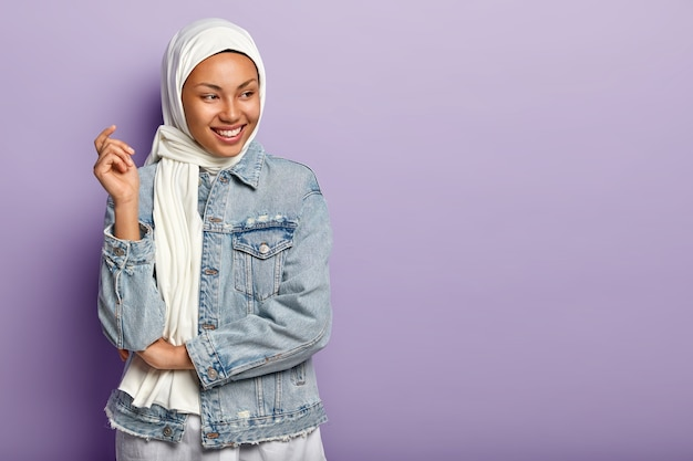 Despreocupada modelo árabe feminina de pele escura ri alegremente, expressa sentimentos sinceros, sorri amplamente, concentrada à parte, posa em touca e jaqueta jeans sobre a parede roxa, espaço em branco