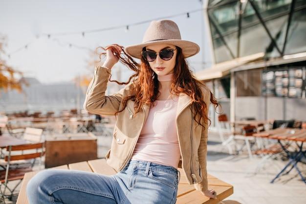 Despreocupada modelo feminina de óculos escuros, posando com chapéu em um café de rua