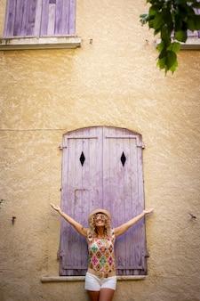 Despreocupada mulher bonita com chapéu de palha em pé com os braços bem abertos na frente da velha porta fechada de madeira da parede do prédio texturizado. mulher hippie desfrutando de liberdade ao ar livre nas férias.