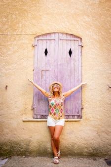 Despreocupada mulher bonita com chapéu em pé com os braços estendidos na frente da janela fechada de madeira velha da parede do edifício texturizado. mulher elegante hippie posando em frente a uma porta fechada ao ar livre na vac