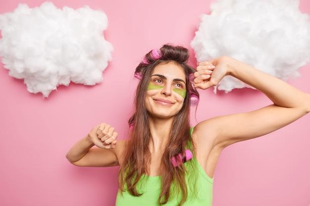 Despreocupada mulher europeia dança despreocupada levanta os braços, estica os braços depois de acordar aplica rolos de cabelo faz penteado para ocasiões especiais passa por tratamentos de pele usa traços verdes sob os olhos