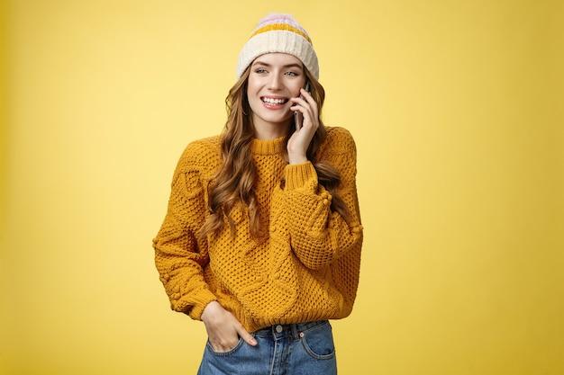 Despreocupada, sociável, mulher simpática e extrovertida, ligando para um amigo, falando alegremente para smartphone, tendo uma conversa divertida e agradável, sorrindo, rindo, olhando para longe segurar o bolso da mão, fundo amarelo em pé