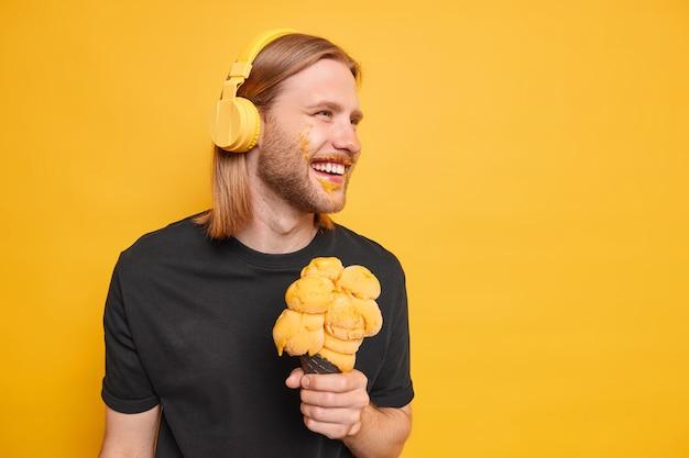 Despreocupado cara hipster com cabelo ruivo sorri positivamente focado longe se diverte, come sorvete saboroso, tem cara suja ouve música através de poses de fones de ouvido contra parede amarela