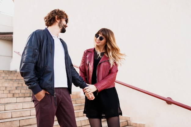 Despreocupado casal apaixonado, andando pela cidade, estilo urbano. menina loira expressiva com seu lindo namorado se divertindo. roupa elegante de primavera.