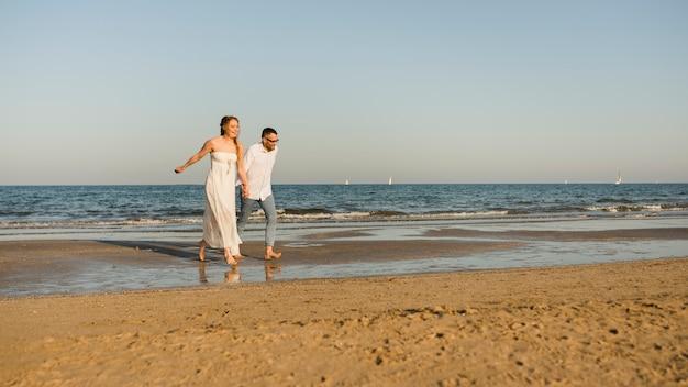 Despreocupado casal segurando a mão do outro correndo na beira-mar