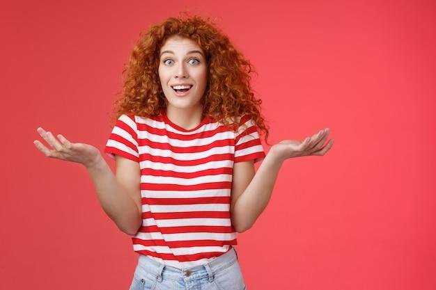 Despreocupado, despreocupado e despreocupado ruiva atraente mulher penteado encaracolado encolhendo os ombros com as mãos desavisadas espalhadas para o lado sorrindo incerto fazendo pergunta amigo intrigante como ela é tão bonita.