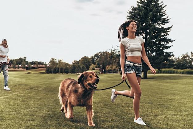 Despreocupado e feliz. comprimento total de uma bela jovem correndo com o cachorro enquanto o namorado dela corria atrás