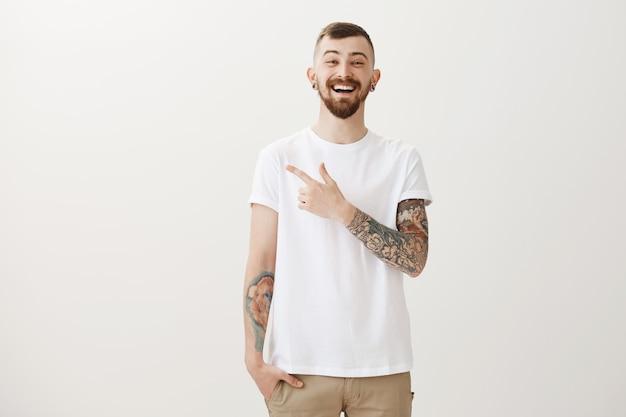 Despreocupado e sorridente cara hipster apontando para a esquerda e rindo