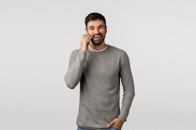 Despreocupado, entusiasmado, barbudo macho de suéter cinza falando no telefone com um sorriso feliz e satisfeito, segure a mão nos bolsos, use chamadas de smartphone via messenger na internet