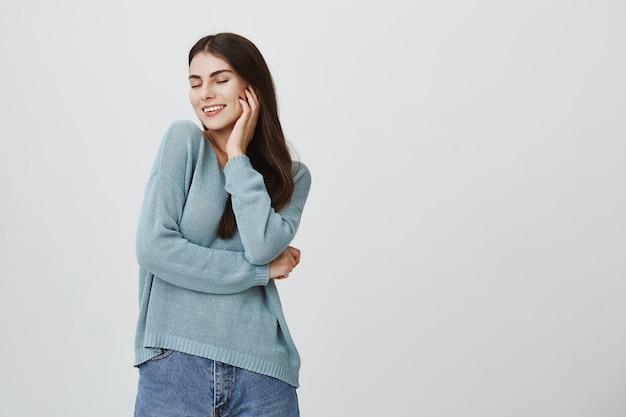 Despreocupado, feliz mulher atraente fechar os olhos e sorrindo