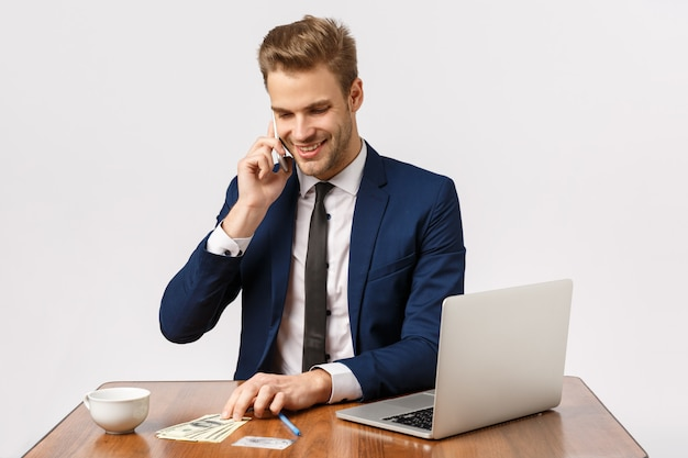 Despreocupado jovem confiante e bem sucedido empresário sentar escritório perto de laptop, beber café, conversando com o gerente de loja on-line, certificando-se de ordem bem, segurando a orelha do smartphone