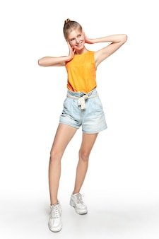 Despreocupado. linda garota com roupa elegante, isolada no fundo branco do estúdio. estilo de revista, moda, conceito de beleza. posando na moda. copyspace para anúncio.
