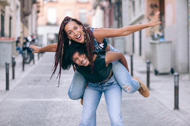 Despreocupado mulheres afro-americanas pulando um no outro