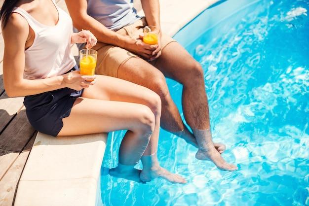 Despreocupado, relaxe na piscina. vista superior de um casal em trajes casuais sentados à beira da piscina e bebendo coquetéis