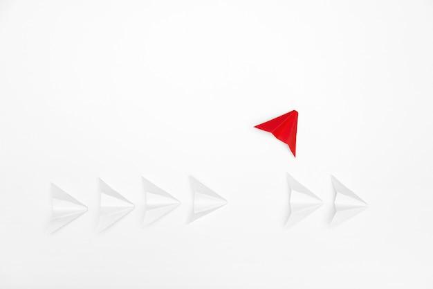 Destacam-se o conceito. avião de papel vermelho, destacando-se da linha de branco