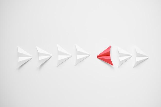 Destacam-se o conceito. avião de papel vermelho, destacando-se da linha de brancos e tentando ser contra todos.