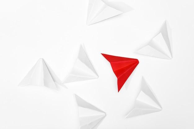 Destacam-se o conceito. avião de papel vermelho, destacando-se dos brancos