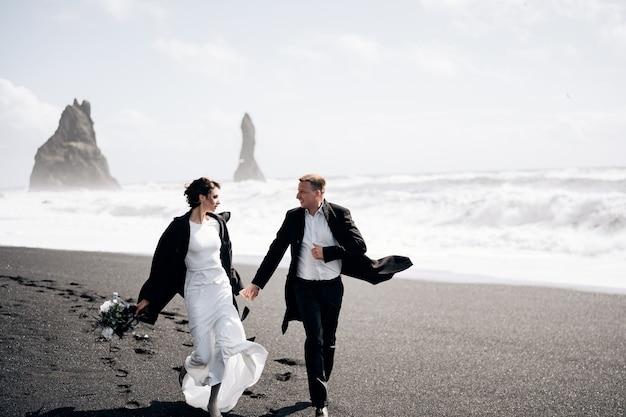 Destino casamento na islândia, o casal de noivos corre ao longo da praia negra de vik, perto do