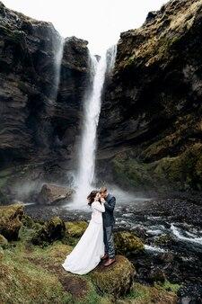 Destino casamento na islândia perto da cachoeira de kvernufoss casal de noivos em pé perto da cachoeira