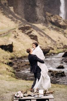 Destino casamento na islândia perto da cachoeira de kvernufoss casal de noivos na costa de uma montanha