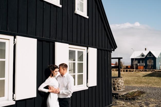 Destino, islândia, casal de noivos, casamento, perto de uma casa de madeira preta com janelas e venezianas brancas