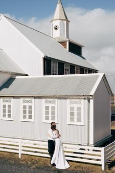 Destino, islândia, casal de noivos, casamento, perto de uma igreja de madeira negra, o noivo abraça a noiva