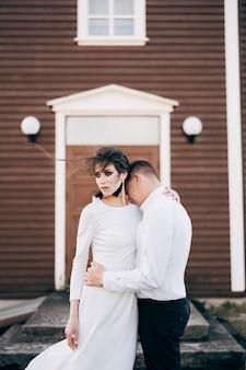 Destino, islândia, casamento, casal de noivos em frente a uma igreja negra, o noivo abraça a noiva