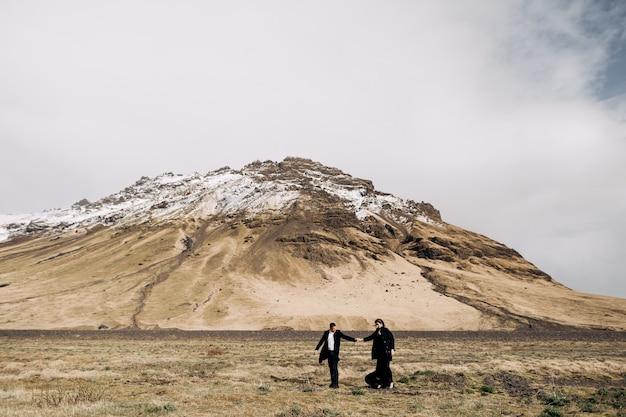 Destino, islândia, casamento, casal, noivos, em um fundo de montanhas nevadas, a noiva e o noivo em