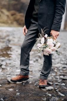 Destino, islândia, casamento, close-up das pernas do noivo segurando um buquê de casamento cinza na mão