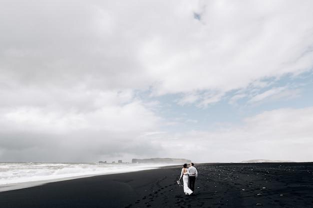 Destino, islândia, casamento, um casal de noivos caminha pela praia negra da praia de areia vic