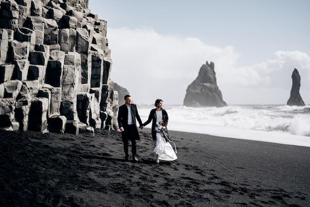 Destino, islândia, casamento, um casal de noivos caminha pela praia negra de vik