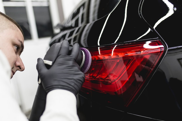Detalhamento de carro - trabalhador com polidor orbital em oficina de automóveis.