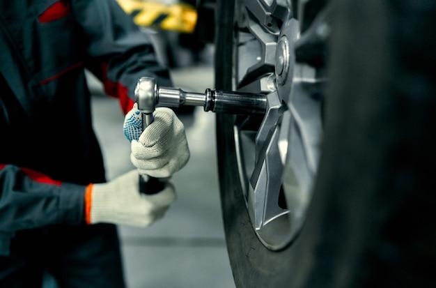 Detalhe a imagem das mãos do mecânico com a ferramenta, trocando o pneu do carro, com o fundo desfocado da garagem.