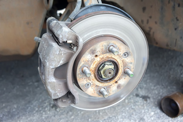Detalhe a imagem das mãos do mecânico com a ferramenta, trocando o pneu do carro, com o fundo desfocado