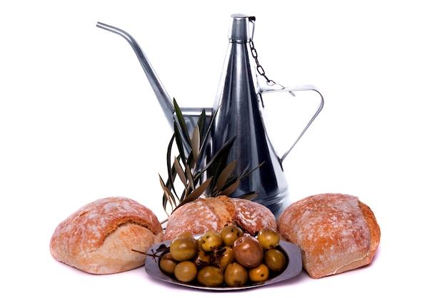 Detalhe a vista de algumas azeitonas em uma placa, em algum pão e em um receptor para o petróleo verde-oliva.