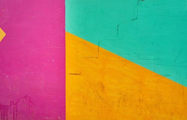 Detalhe abstrato de parede com fragmentos de grafite colorido.