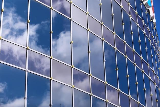 Detalhe arquitetônico da fachada com múltiplos reflexos de outras construções e do sol. exterior do edifício moderno. arquitetura de fundo abstrato