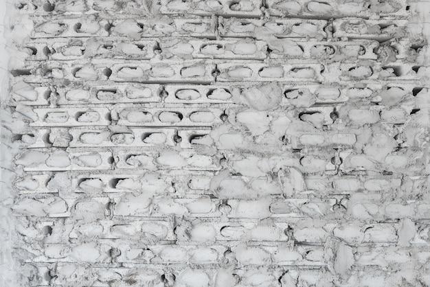 Detalhe arquitetônico incompleto cinza parede de tijolos de concreto sob construção