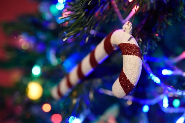 Detalhe bastão de doces na árvore de natal com bokeh
