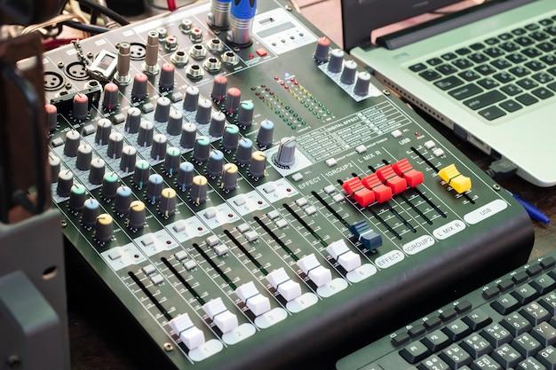 Detalhe com botões de ajuste em um mixer de áudio profissional e equipamento de música para controle de mixer de som