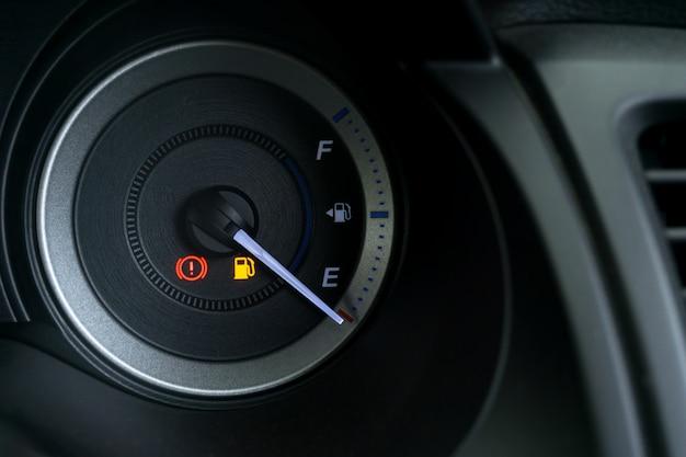 Detalhe com os indicadores de combustível mostrando e tanque vazio no painel do carro