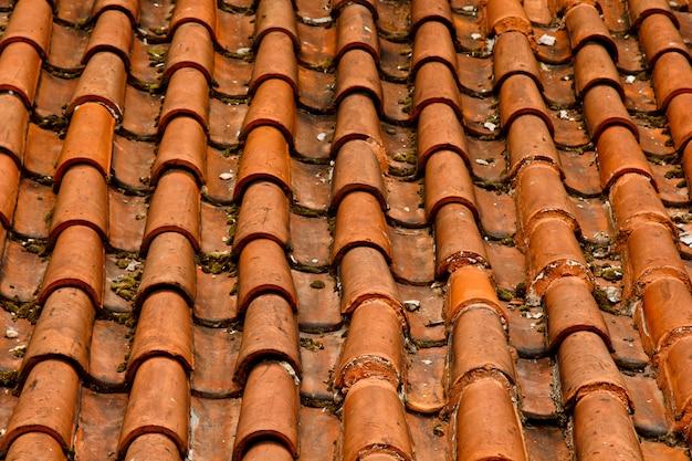 Detalhe com pouca luz da parte superior do telhado vermelho da pátina. material de cobertura típico de praga lesser town. telhados antigos de telhas de barro. vários tons de laranja e manchas.