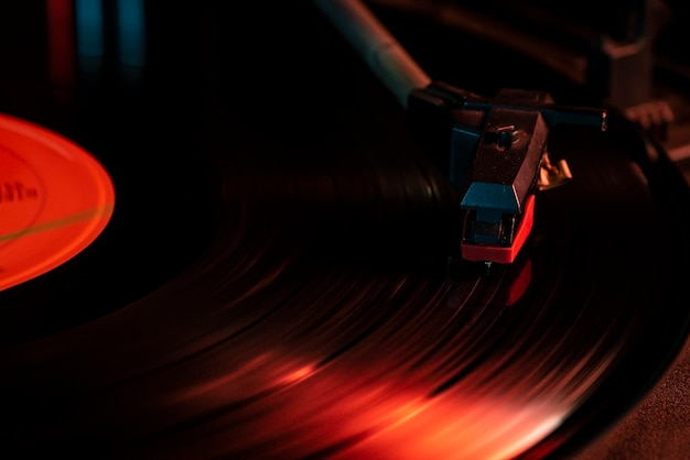 Detalhe da agulha no disco de vinil na plataforma giratória, imagem de luz fraca com reflexo