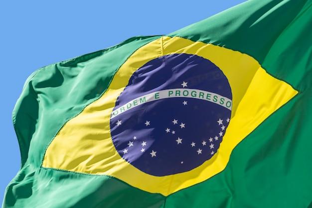 Detalhe da bandeira do brasil tremulando no céu azul. ordem e progresso, em português. bandeira brasileira