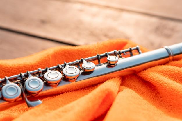 Detalhe da chave da flauta de prata brilhando pela luz do sol no pano laranja, instrumento de sopro de metal elegante para educação de estudantes de música