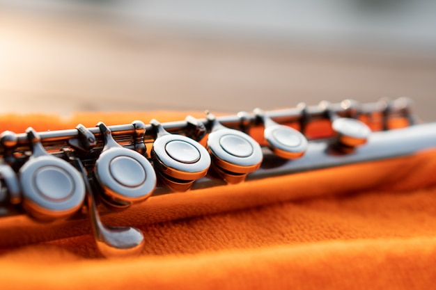 Detalhe da chave de flauta de prata brilhando pela luz do sol no pano laranja